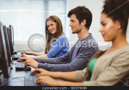 Happy student in computer class smiling at camera stock photo, Happy student in computer class smiling at camera at the university by Wavebreak Media