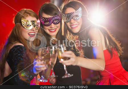 Friends in masquerade masks toasting with champagne stock photo, Friends in masquerade masks toasting with champagne at the nightclub by Wavebreak Media