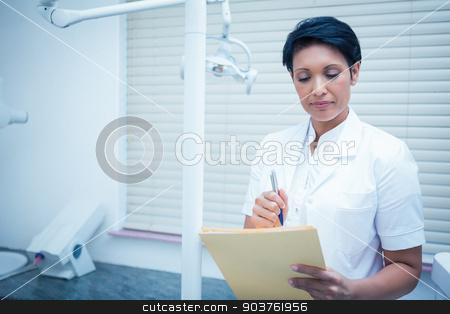 Female dentist reading reports stock photo, Serious female dentist reading reports by Wavebreak Media