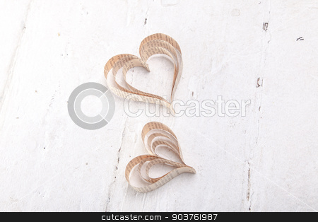 Heart-shaped cutout St Valentines hearts stock photo, Vintage book heart shaped cutout on bleached board texture background by Oleksandr Solonenko