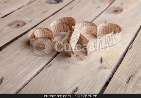 Heart-shaped cutout St Valentines hearts stock photo, Vintage book heart shaped cutout on rough wood board texture background by Oleksandr Solonenko