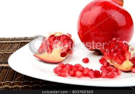 Studio shot open pomegranate on plate wooden mate stock photo, Studio shot of open pomegranate with red seeds on brown wooden mate on plate by Tadeusz Wejkszo