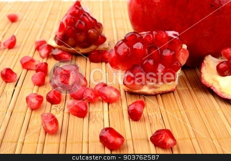 Studio shot open pomegranate on bright wooden mate stock photo, Studio shot of open pomegranate with red seeds on bright wooden mate by Tadeusz Wejkszo