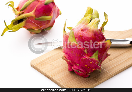 Two Pitayas, One Kitchen Knife And A Cutting Board stock photo, Close-up of a whole dragonfruit and a kitchen knife placed on a wooden cutting board. A second entire pitaya is placed behind on the clean white table top. Lush colors. Vibrant pink and magenta. by Leo Wolfert
