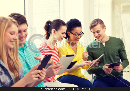 smiling students with tablet pc at school stock photo, education, technology and internet concept - smiling students looking at tablet pc computer at school by Syda Productions