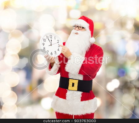 man in costume of santa claus with clock stock photo, christmas, holidays and people concept - man in costume of santa claus with clock showing twelve pointing finger over lights background by Syda Productions