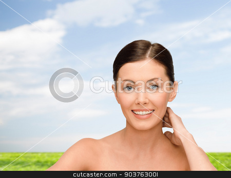 smiling young woman with bare shoulders stock photo, beauty, people and health concept - smiling young woman with bare shoulders over blue sky and grass background by Syda Productions