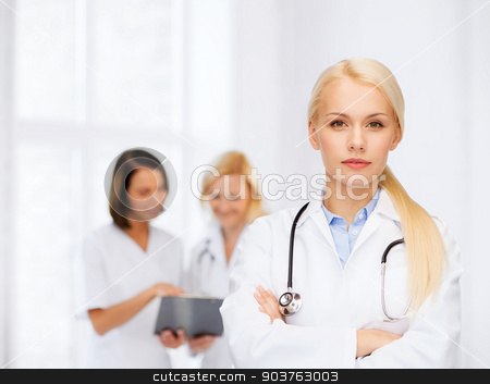 serious female doctor with stethoscope stock photo, healthcare and medicine concept - serious female doctor with stethoscope by Syda Productions