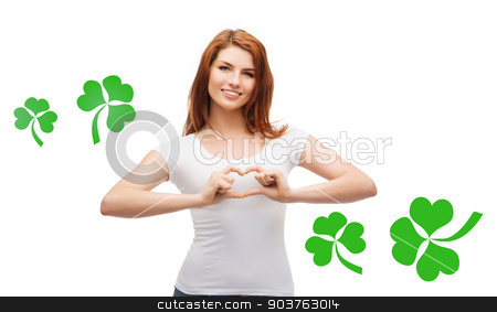 smiling girl showing heart gesture with shamrock stock photo, gesture, holidays, st. patricks day and happy people concept - smiling girl in white blank t-shirts showing heart with hands over white background with green shamrock or clover by Syda Productions