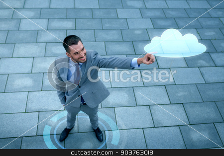 smiling businessman with cloud projection outdoors stock photo, business, development, technology and people and concept - young smiling businessman pointing finger to cloud projection outdoors from top by Syda Productions