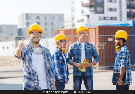 group of smiling builders in hardhats outdoors stock photo, business, building, teamwork, gesture and people concept - group of smiling builders in hardhats showing thumbs up outdoors by Syda Productions