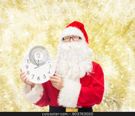 man in costume of santa claus with clock stock photo, christmas, holidays and people concept - man in costume of santa claus with clock showing twelve over yellow lights background by Syda Productions