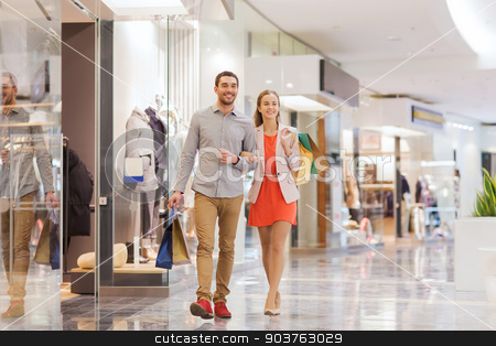 happy young couple with shopping bags in mall stock photo, sale, consumerism and people concept - happy young couple with shopping bags walking in mall by Syda Productions