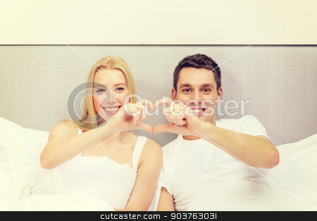 smiling couple showing heart with hands stock photo, hotel, travel, relationships and happiness concept - smiling couple with champagne glasses in bed by Syda Productions