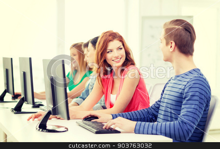 smiling students in computer class at school stock photo, education, technology and school concept - smiling students in computer class at school having discussion by Syda Productions