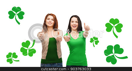 two smiling girls showing thumbs up with shamrock stock photo, gesture, holidays, st. patricks day and happy people concept - two smiling girls showing thumbs up over white background with green shamrock or clover by Syda Productions