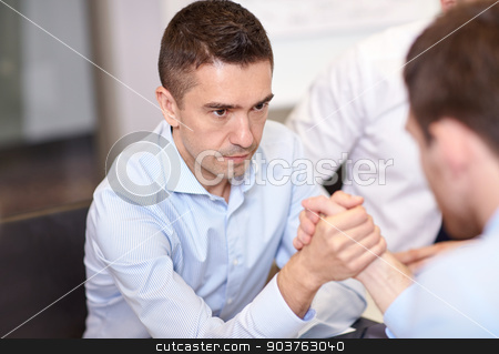 businessmen arm wrestling in office stock photo, business, people, crisis and confrontation concept - businessmen arm wrestling in office by Syda Productions