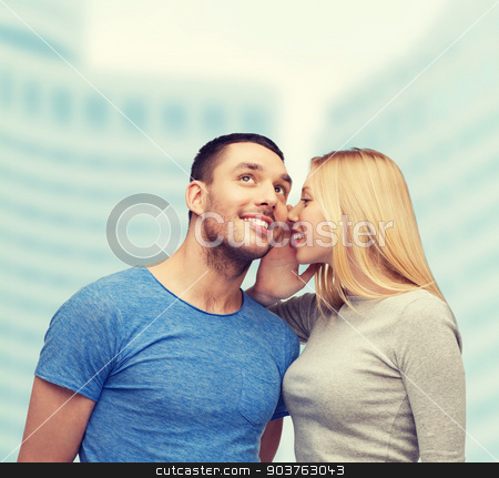 smiling girlfriend telling boyfriend secret stock photo, relationships, love and couple concept - smiling girlfriend telling boyfriend secret by Syda Productions