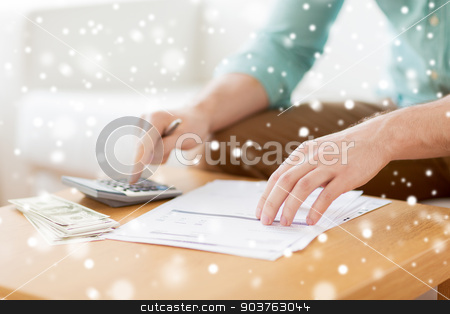 close up of man counting money and making notes stock photo, savings, finances, paperwork and people concept - close up of man with calculator counting money and making notes at home by Syda Productions