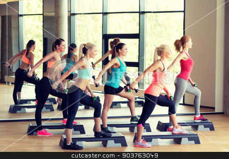 group of women with dumbbells and steppers stock photo, fitness, sport, training, gym and lifestyle concept - group of women working out with dumbbells and steppers in gym by Syda Productions