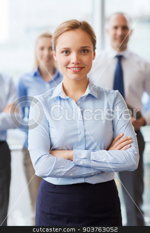 smiling businesswoman with colleagues in office stock photo, business, people and teamwork concept - smiling businesswoman with group of businesspeople in office by Syda Productions