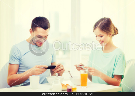 smiling couple with smartphones taking picture stock photo, food, home, couple and technology concept - smiling couple with smartphones teaking picture of breakfast at home by Syda Productions