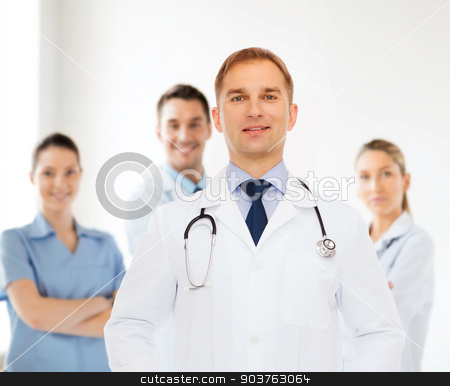 smiling male doctor with stethoscope stock photo, healthcare, profession, teamwork, people and medicine concept - smiling male doctor with stethoscope in white coat over over group of medics by Syda Productions