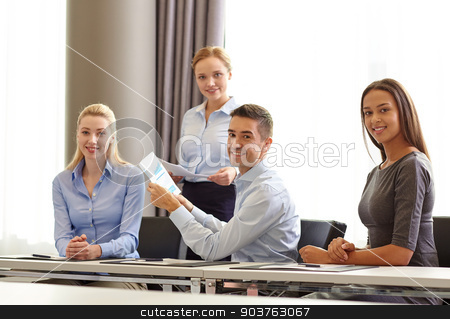 smiling business people with papers in office stock photo, business, people and teamwork concept - smiling business team with papers meeting in office by Syda Productions