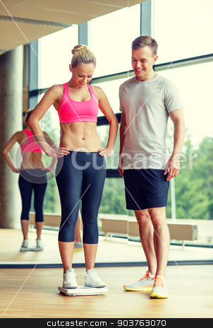 smiling man and woman with scales in gym stock photo, sport, fitness, lifestyle and people concept - smiling man and woman with scales in gym by Syda Productions