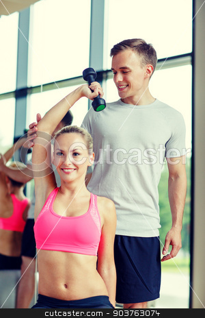 smiling young woman with personal trainer in gym stock photo, fitness, sport, exercising and diet concept - smiling young woman and personal trainer with dumbbell in gym by Syda Productions