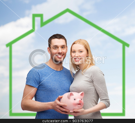 smiling couple holding piggy bank over green house stock photo, love, home, people and family concept - smiling couple holding piggy bank over green house and blue sky with grass background by Syda Productions