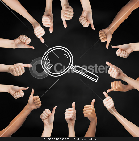 hands showing thumbs up in circle over magnifier stock photo, gesture, people and exploration concept - human hands showing thumbs up in circle over black board background with magnifier by Syda Productions