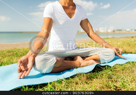 close up of man making yoga exercises outdoors stock photo, fitness, sport, people and lifestyle concept - close up of man making yoga exercises on mat outdoors by Syda Productions