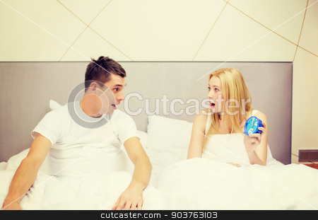 surprised couple with clock in bed stock photo, hotel, travel, relationships and happiness concept - surprised couple with clock in bed by Syda Productions