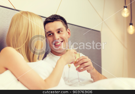 smiling couple with champagne glasses in bed stock photo, hotel, travel, relationships and happiness concept - smiling couple with champagne glasses in bed by Syda Productions