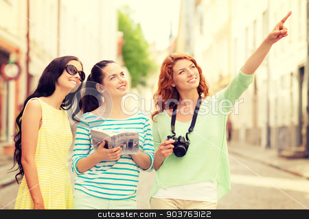 smiling teenage girls with city guide and camera stock photo, tourism, travel, leisure, holidays and friendship concept - smiling teenage girls with city guide and camera outdoors by Syda Productions