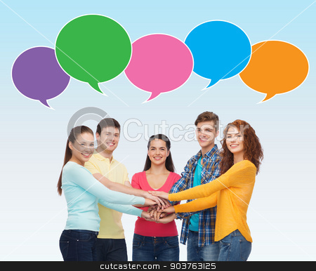 smiling teenagers with hands on top of each other stock photo, friendship, communication, gesture and people concept - group of smiling teenagers with hands on top of each other over blue background with text bubbles by Syda Productions