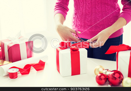 close up of woman decorating christmas presents stock photo, holidays, people and celebration concept - close up of woman decorating christmas presents by Syda Productions