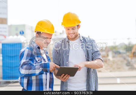 smiling builders in hardhats with tablet pc stock photo, business, building, teamwork, technology and people concept - group of smiling builders in hardhats with tablet pc computer outdoors by Syda Productions