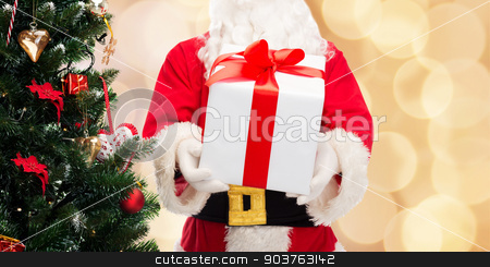 man in costume of santa claus with gift box stock photo, christmas, holidays and people concept - close up of santa claus with gift box and tree over beige lights background by Syda Productions