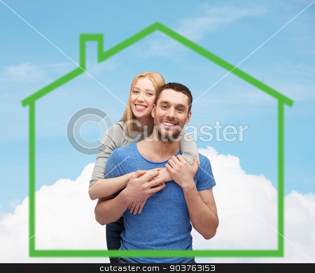 smiling couple hugging over green house stock photo, love, home, people and family concept - smiling couple hugging over green house and blue sky with cloud background by Syda Productions