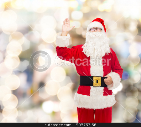 man in costume of santa claus stock photo, christmas, holidays, gesture and people concept - man in costume of santa claus waving hand over lights background by Syda Productions