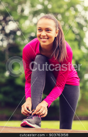 smiling woman exercising outdoors stock photo, sport, exercise, park and lifestyle concept - smiling african american woman exercising outdoors by Syda Productions