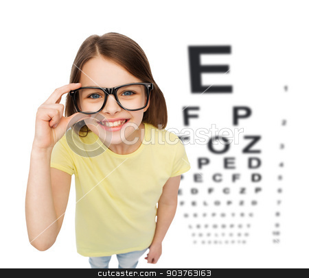 smiling little girl in eyeglasses with eye chart stock photo, people, childhood, healthcare and vision concept - smiling little girl in black eyeglasses over white background with eye chart by Syda Productions