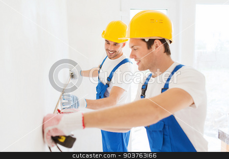 smiling builders with measuring tape indoors stock photo, building, teamwork, measurement and people concept - group of smiling builders in hardhats measuring wall with tape working indoors by Syda Productions