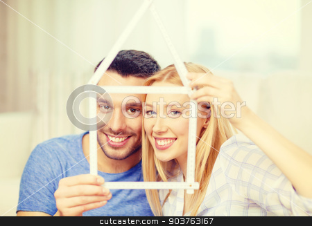 smiling couple with house from measuring tape stock photo, moving, home and couple concept - smiling couple with house from measuring tape at new home by Syda Productions