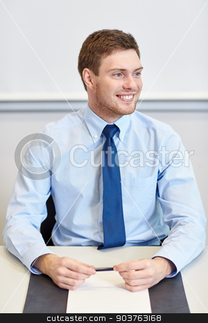 smiling businessman sitting in office stock photo, business, people and work concept - smiling businessman sitting in office in front of whiteboard by Syda Productions