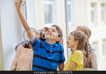 group of school kids taking selfie with smartphone stock photo, education, elementary school, drinks, children and people concept - group of school kids taking selfie with smartphone in corridor by Syda Productions