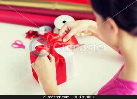 close up of woman decorating christmas presents stock photo, holidays, people and celebration concept - close up of woman decorating christmas present by Syda Productions