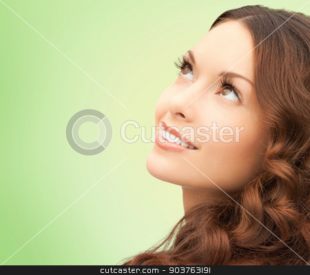 beautiful young woman face stock photo, beauty, people and health concept - beautiful young woman looking up over green background by Syda Productions